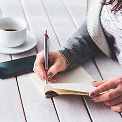 chica-planificar-en-agenda-escritos-con-taza-de-café-y-el-móvil-a-su-lado