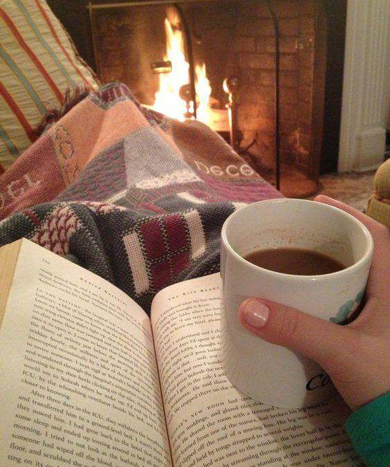persona-leyendo-un-libro-frente-a-la-chimenea-con-una-taza-en-la-mano