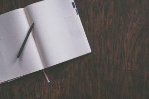 Libreta-abierta-para-planificar-escritos-sobre-mesa-de-madera