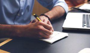 mano-con-lapiz-amarillo-escribiendo