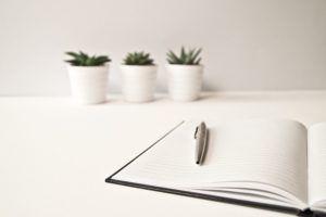 mesa-blanca-con-libreta-y-bolígrafo-y-tres-macetas-de-fondo