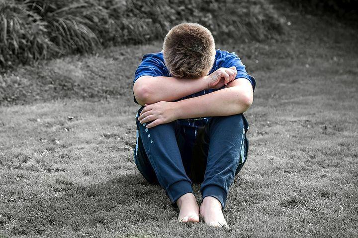 chico-con-miedo-sentado-y-escondiendo-la-cabeza-en-las-rodillas