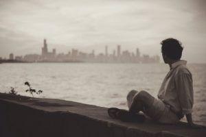 joven-sentado-en-muell-mirando-la-ciudad-desde-lejos