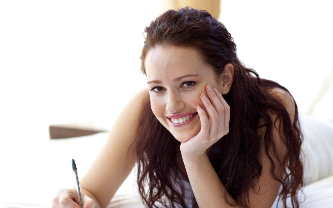 joven-mirando-sonriente-recostada-en-cama-escribiendo