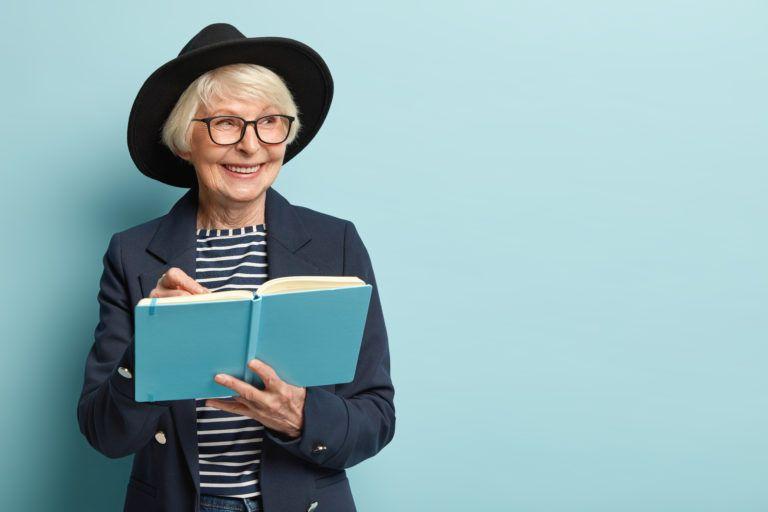 mujer-mayor-con-sombrero-sonriendo-mientras-escribe