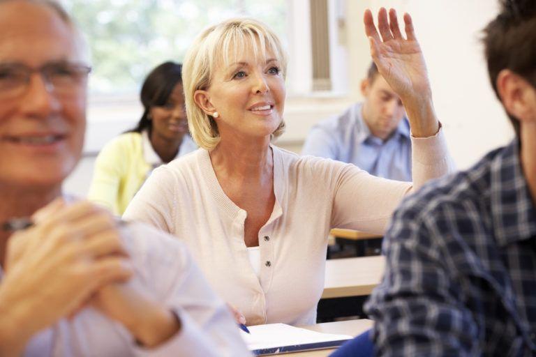 mujer-madura-en-clase-levantando-la-mano-para-preguntaf