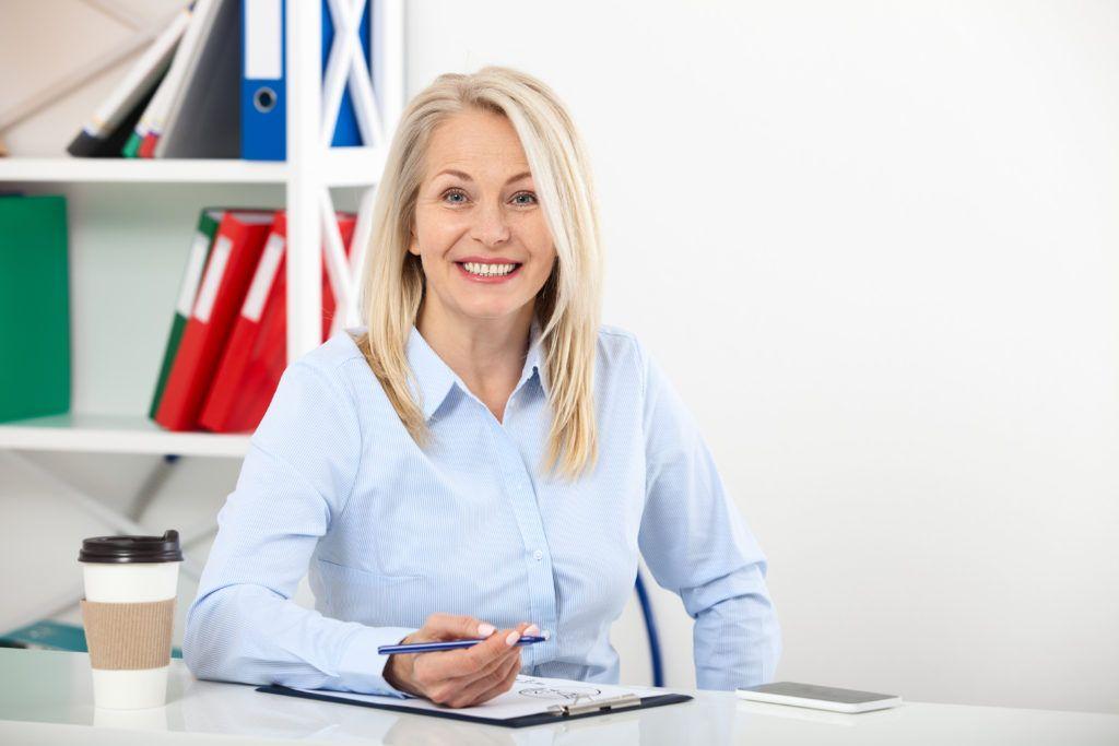 Mujer-madura-sonriendo-mientras-escribe