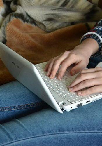 chica-escribiendo-con-portatil-sobre-las-piernas