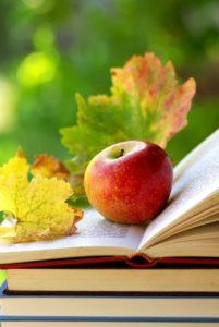 manzana-sobre-libro-abierto-con-hojas-de-parra-de-decoracion