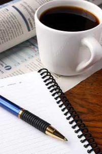 taza-de-cafe-con-una-libreta-y-boligrafo-a-su-lado