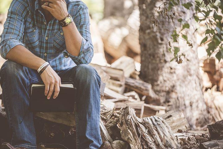 hombre-sentado-en-un-tronco-con-libro-en-la-mano