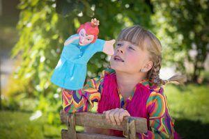 niña-visualiza-una-marioneta-en-un-campo-jugando