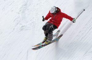 hombre-con-anorak-rojo-esquiando-por-pendiente