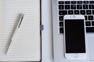 mesa-con-movil-pantalla-libreta-bolígrafo-ordenador
